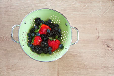 Strawberries, blueberries and blackberries in a colander on a natural wood surface photo