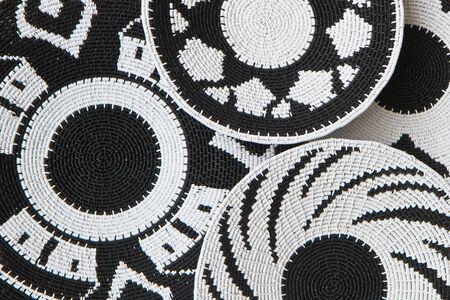 Gevlochten manden als achtergrond gemaakt met zwarte en witte plastic gecoat telefoondraad door Afrikaanse ambachtslieden