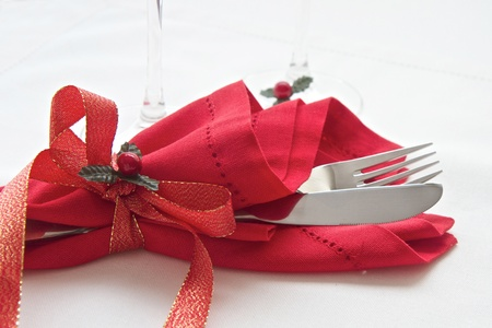 serviette: Knife and fork wrapped in a red napkin with holly and ribbon Stock Photo