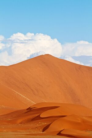 Sand dunes of the Namibian desert with clouds and sky Stock Photo
