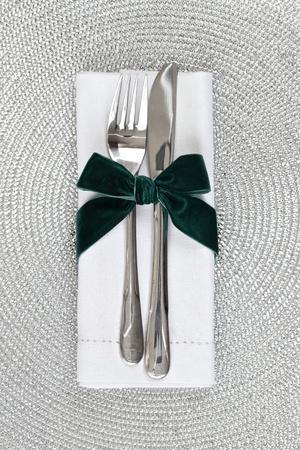 cubiertos de plata: Cuchillo y tenedor envuelto en cinta de terciopelo verde para la Navidad Foto de archivo
