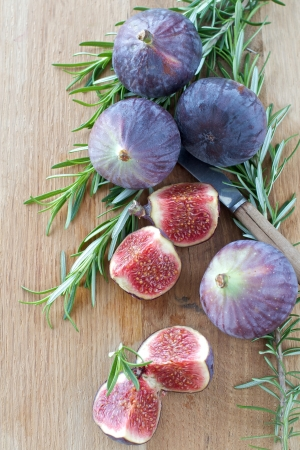 Fresh Figs and Rosemary on a wooden board Stock Photo