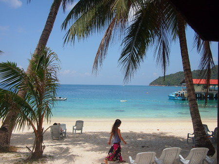 perhentian: Pulau Perhentian Besar, Malaysia - March 5, 2015: View from a beach hut balcony, overlooking the white sand and turquoise sea, with a young woman going for a morning stroll.