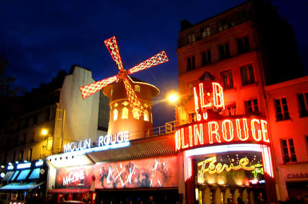 moulin: Paris, France - April 12, 2012: The Moulin Rouge is a famous cabaret built in 1889, located in the Paris red-light district of Pigalle. Its illuminated lights can be seen from all around at night time.