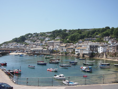 incidental people: Mousehole, Cornwall, UK - July 11, 2015: A small harbour in the Cornish village of Mousehole in the summer