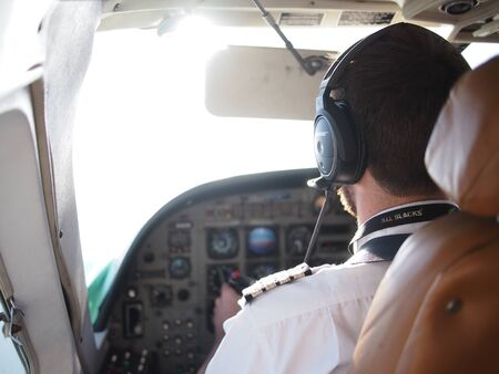 seater: Selous Game Reserve, Tanzania - November 21, 2015: View of a a young male pilot and the cockpit as he flies a smaller 18 seater plane into the Selous Game Reserve in Southern Tanzania.