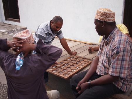local 27: Stone Town, Zanzibar, Tanzania - November 27, 2015: Three local men play a tradition Tanzanian board game called Bao Editorial