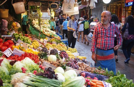 veg: stanbul, Turkey - September 26, 2015: Tourists and locals walking past the fruit and veg market stall and its owner on the Asian side of Istanbul.