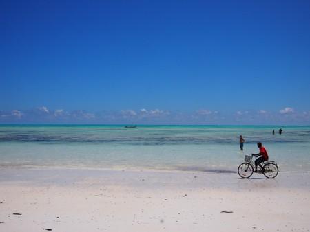 high tide: Jambiani Beach, Zanzibar, Tanzania - December 1, 2015: One man cycles along the deserted and stunning Jambiani beach on the East cost of Zanzibar during high tide