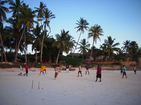 locals: Kizimkaze, Zanzibar, Tanzania - December 1, 2015: Locals play beach football on Zanzibar island as the sun sets