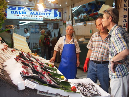selling service: Istanbul, Turkey - September 26, 2015: A local fish vendor sells fresh fish to people at a food market on the Asian side of Istanbul.