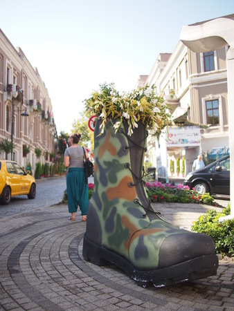 upmarket: Istanbul, Turkey - September 26, 2015: Tourists and a giant boot monument in the upmarket Besiktas area of Istanbul. Stock Photo