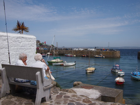 two people only: Mousehole, Cornwall, UK - July 11, 2015: Two elderly women sit and watch the people in a small harbour in Cornwall