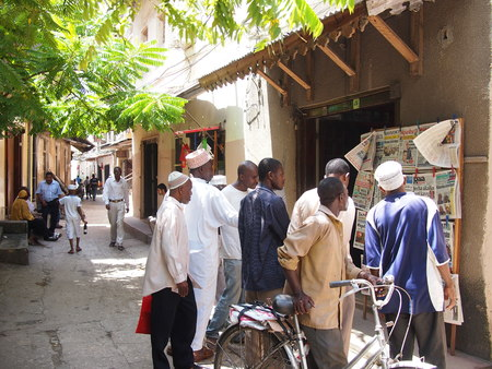 local 27: Stone Town, Zanzibar, Tanzania - November 27, 2015: A group of local men crowd round a shop to read the newspapers in Zanzibars capital. Nobody actually buys the paper, they just all read it from a distance.