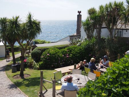 mousehole: Mousehole, Cornwall, UK - July 11, 2015: Guests drink in the sunshine in a pub beer garden with a sea view
