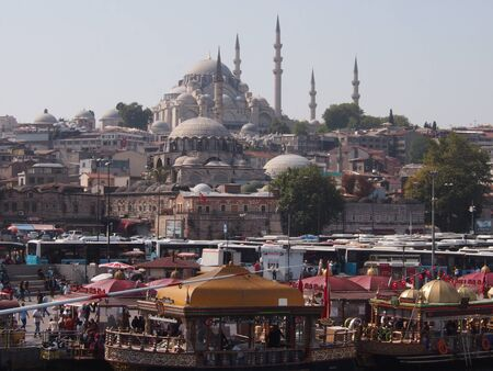 turkish ethnicity: Istanbul, Turkey - September 27, 2015: Fish market selling to tourists at Galata Bridge in front of a mosque in Istanbul.