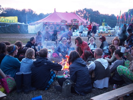 wind down: Pilton, United Kingdom - June 29, 2015: Music festival crowd at sunrise after a night of partying. Most try and wind down with a hot cup of tea around the fire.