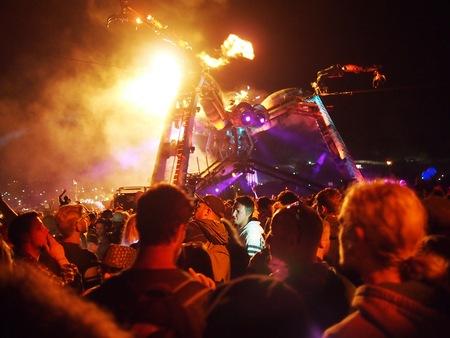 under fire: Pilton, Reino Unido - 28 de junio de 2015: Festival de música de baile multitud bajo la tarántula gigante de respiración del fuego Editorial