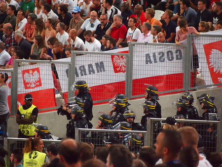 violence in sports: Marseille, France - June 30, 2016: Riot police monitor Polish fans during their quarter final defeat to Portugal in the Euros