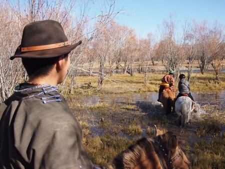 Gorkhi Terelj National Park, Mongolia - 01 October, 2016: Mongolian herder crossing a river on horseback Stock Photo