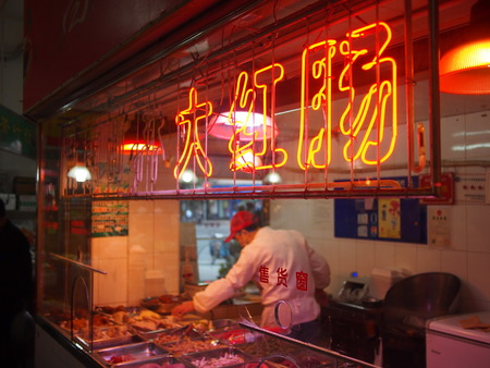 Shanghai, China - 14 October 2016: Chinese meat market with illuminated neon sign