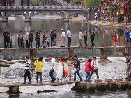 Fenghuang, China - 18 October, 2016: Tourists struggle to cross the narrow footbridge across the river in Fenghuangs old town. Many stop to take photos, just clogging up the bridge even more. Editorial