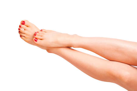 Smooth feminine legs with red nails in studio photo