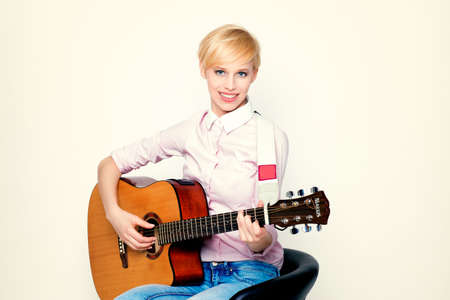 woman guitar: An attractive young woman playing acoustic guitar Stock Photo