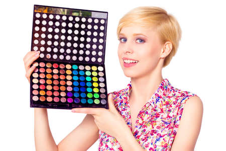 beautification: Artis with makeup brushes and palette of eyeshadows