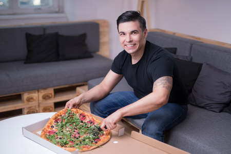 Young handsome man eating pizzas in his apartment alone