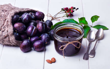 linen bag: Plum jam in a jar on a white table and plums in a linen bag