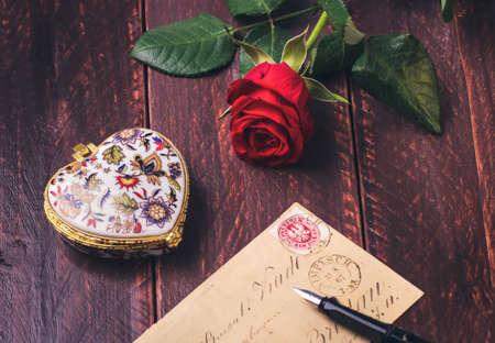 Rote Rose auf einem alten Liebesbrief-Konzept auf Holz Tisch.