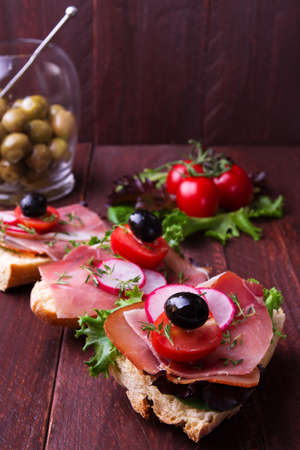 carnes y verduras: Spanish ham baguette with tomato and olive on a dark wooden table