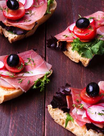 carnes y verduras: baguette de jamón español con tomate y aceite de oliva en una mesa de madera oscura Foto de archivo