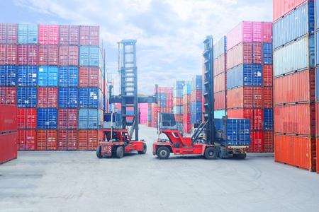 Gabelstapler, der Frachtcontainer im Versandhof oder Dockyard gegen Sonnenaufganghimmel anhebt, mit Frachtcontainerstapel im Hintergrund für Transportimport, -export und logistisches Industriekonzept Editorial