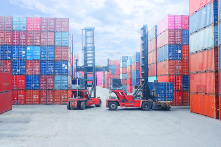 Wózek widłowy podnoszący kontener ładunkowy w stoczni lub stoczni przed wschodem słońca ze stosem kontenerów w tle do transportu, importu, eksportu i logistycznej koncepcji przemysłowej Publikacyjne