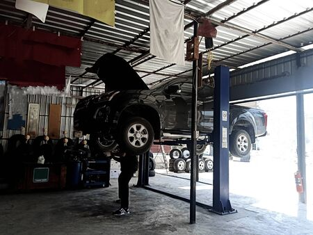 The mechanic is fixing the lower part of the car Pictures about the automotive industry