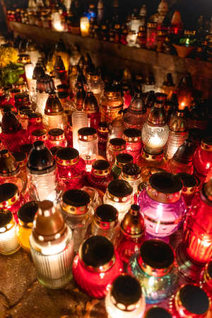 Close-up shot of lit up candles burning at Polish cemetery during All Saints day celebrations in November in Poland