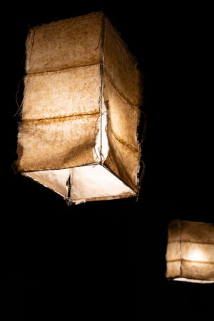 Japanese style ceiling lamps with fabric panels glowing in the dark seen from below