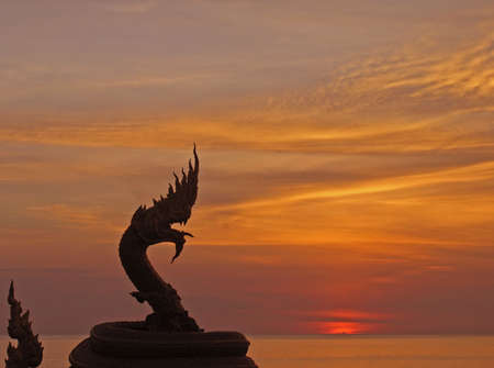 Statue of a dragon taken at sunset, giving the impression of fire coming out of its mouth photo