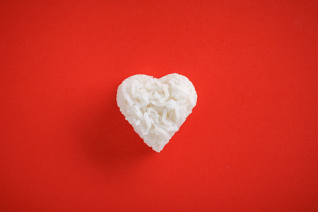 Top view of heart shaped cooked  rice on red background.