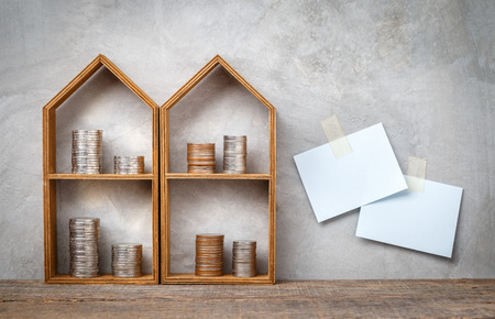 Little house shelf with coins stacked on wooden plank and grey concrete wall with note paper attached. Фото со стока