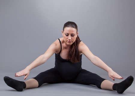 Pregnant woman doing gymnastic exercises on grey background. Stock Photo - 12568179