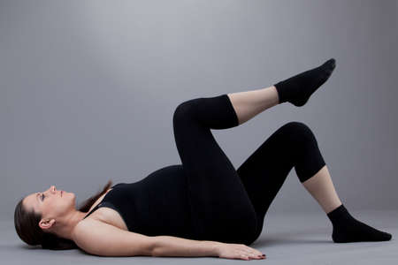 Pregnant woman doing gymnastic exercises on grey background. Stock Photo - 12568080
