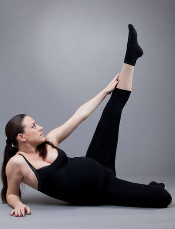 Pregnant woman doing gymnastic exercises on grey background. Stock Photo - 12568169