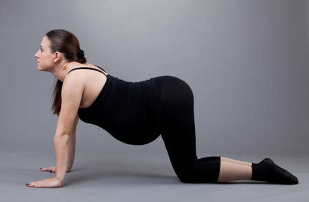 Pregnant woman doing gymnastic exercises on grey background. Stock Photo - 12568157
