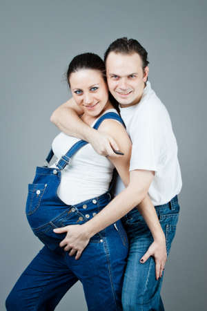A man and a pregnant woman, the couple posing on a gray background Stock Photo - 15616174