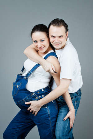 A man and a pregnant woman, the couple posing on a gray background Stock Photo - 15616172