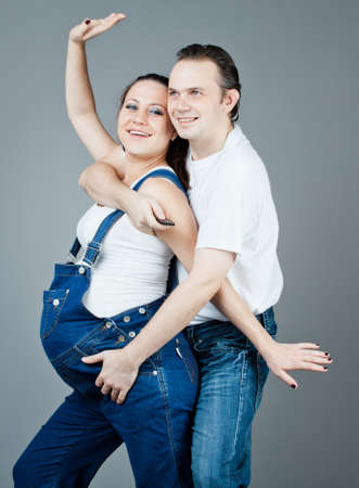 A man and a pregnant woman, the couple posing on a gray background Stock Photo - 15616185