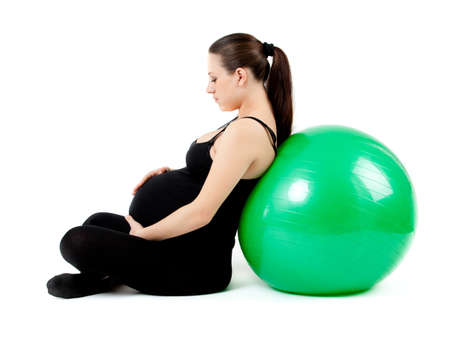 Pregnant woman excercises with gymnastic ball. Stock Photo